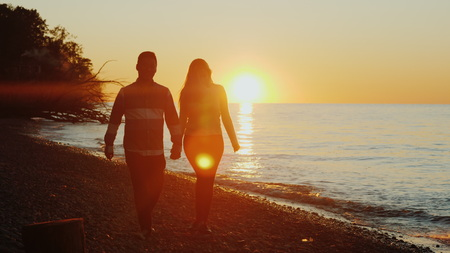 A young couple with a sob will admire the beautiful sunset over Lake Ontario. Chinese man and Caucasian woman Banco de Imagens