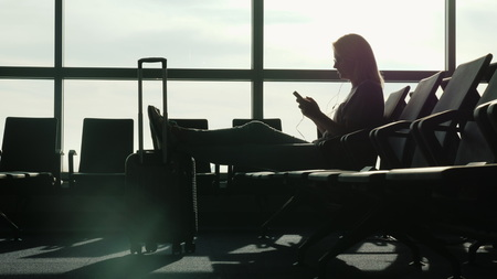 A woman is sitting in the terminal of the international airport, waiting for her flight. Uses a smartphone.