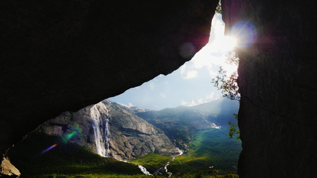 The sun shines through the arch in the rock, where you can see the picturesque valley surrounded by high mountains. The amazing nature of Norway, the tourists dream Banco de Imagens