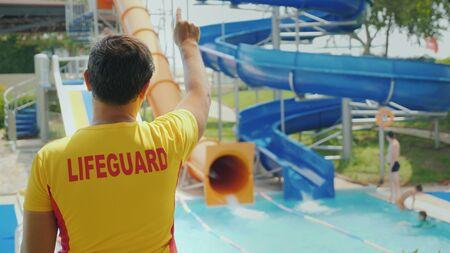 A man lifeguard is on duty near water slides