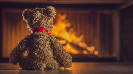 Teddy bear is heated near the fireplace. Warm and cozy home concept
