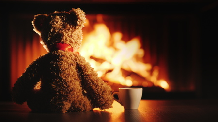 A bear cub with a cup of tea sits opposite the fireplace. Comfort and warmth in the house Stok Fotoğraf