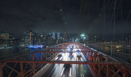 Traffic cars over the Brooklyn Bridge. Against the backdrop of the silhouette of the night in New York Stock fotó