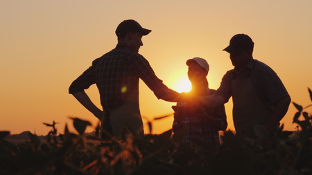 Un grupo de agricultores en el campo, dándose la mano. Agroindustria familiar