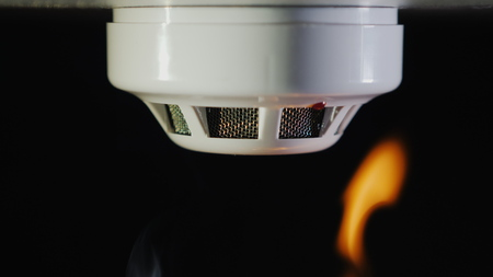 Close-up shot: The smoke detector is triggered by a trickle of dum, the red indicator lights up