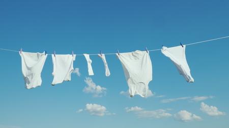 Weißes Leinen trocknet am Seil gegen den blauen Himmel
