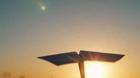 A paper airplane is flying in the sky to meet the setting sun. Rear view Stock Photo