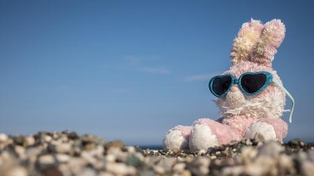 Plush rabbit in sunglasses sits on a pebble beach by the sea Reklamní fotografie