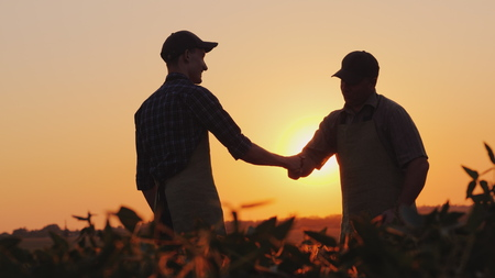 Senior farmer shakes hands with a young colleague. Smile, positive emotions