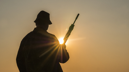 Silhouette of a hunter with a gun, the suns rays shine in his face