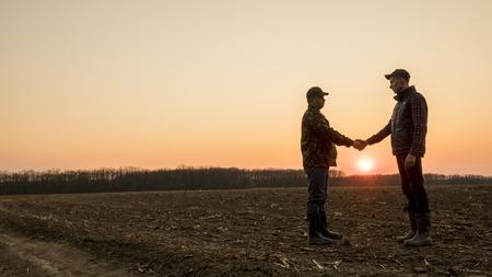 Dos agricultores en el campo se dan la mano al atardecer. Disparo de lente amplia