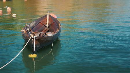 Un bateau de pêche est amarré au rivage. Se balançant lentement sur une vague par une claire journée d'été Banque d'images