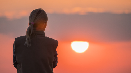 A silhouette of a woman looking at a big red sun Stock Photo