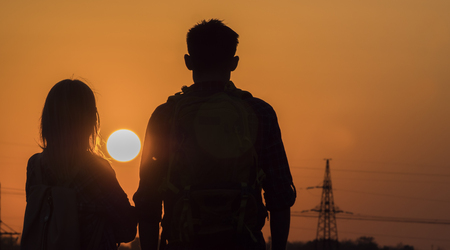 Two teenagers look forward to the sunset of a large sun over the city