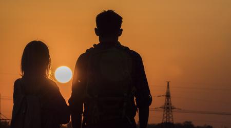 Zwei Teenager freuen sich auf den Sonnenuntergang einer großen Sonne über der Stadt Standard-Bild