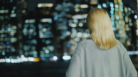 Woman looks at the lights of the night metropolis, rear view Stock Photo
