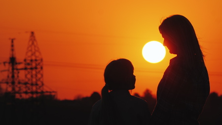 Woman looks at her daughter on the background of the sunset over the city