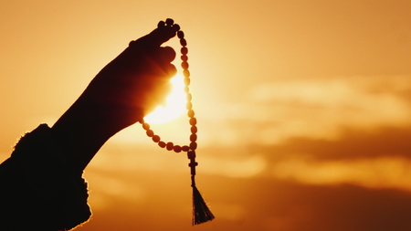 Hand holds rosary against the sky and the setting sun, sincere prayer and meditation