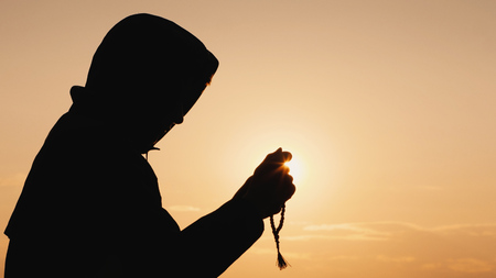 A man in a robe meditates at sunset, goes through the rosary in his hands