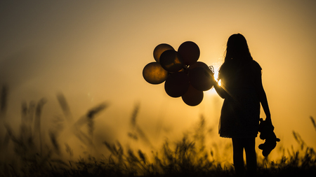 Silhouette of a girl with balloons and a teddy bear. It is worth the sunset. Farewell to childhood concept