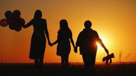 Madre hija y abuela juntas admiran la puesta de sol. Concepto de personas mayores activas Foto de archivo