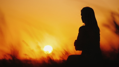 Silhouette of a woman in high grass at sunset. Grass swaying in the wind