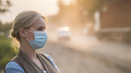 A woman in a protective mask on a dusty road. Ecology problems concept