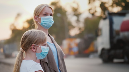 A woman with a child in protective masks are standing near a dirty, dusty road in the city