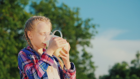 A child drinks milk from a jug on a background of green trees. Fresh and healthy foods