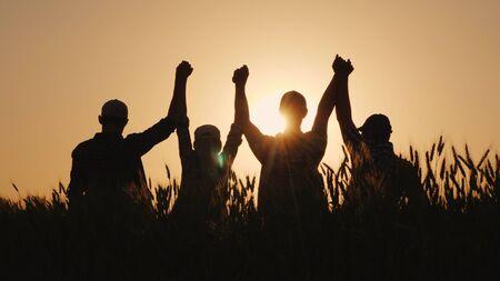 Een groep succesvolle jonge mensen houdt elkaars hand vast, samen steken ze de bovenhand. Succesvol team en teambuilding concept.