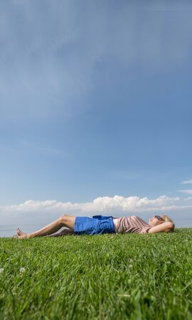 Happy barefoot woman lies on the green grass, rejoices in the heat and summer
