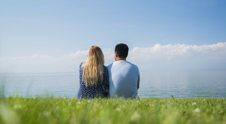 A young couple is sitting on a green lawn in a picturesque place near the lake
