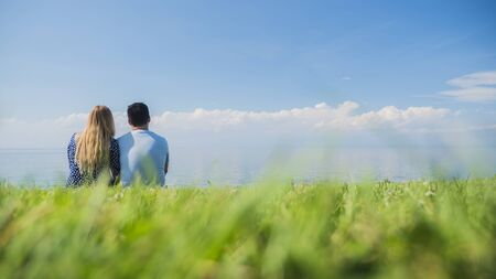 Multi-ethnic couple resting on the green grass, admiring the beautiful nature Imagens