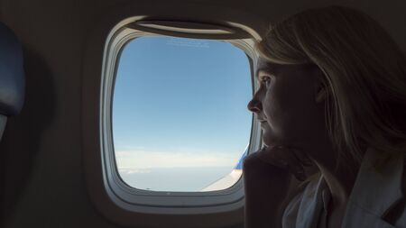 Pensive woman looking out the window of an airplane