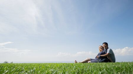 Asian man with a pregnant woman are resting in nature in a picturesque place, sit on the green grass