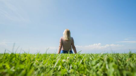 A woman is sitting on perfect shorn grass that goes into a clear blue sky Stok Fotoğraf