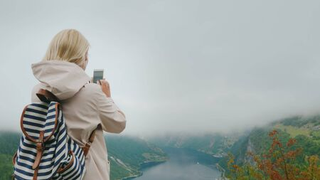 Woman traveler photographs a scenic view of the fjord in Norway, a trip to Scandinavia Imagens