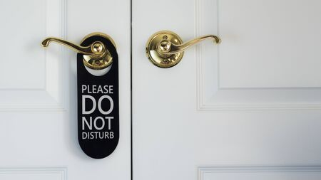 The plate on the door Do not disturb. Hanging on the white door in the hotel