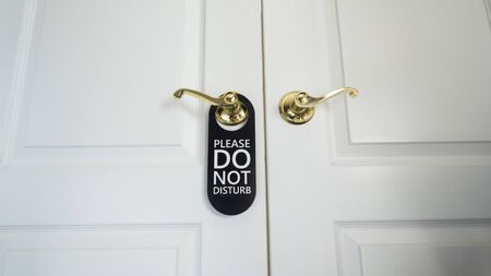 Do not disturb sign hanging on the door of a hotel room