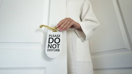 Unrecognizable woman in a white house coat hangs a sign on the door Do not disturb Imagens