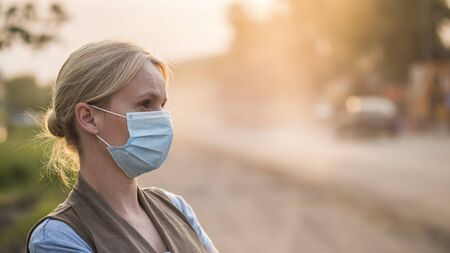 A woman in a gauze bandage is on a dusty road. Environment and ecology concept Imagens