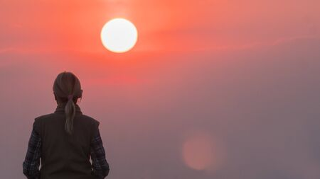 The lonely power of women against the pink sky and the large disk of the red sun Imagens