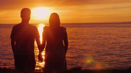 Romantic multi-ethnic couple admires the scenic sunset over the sea. Holding hands, rear view. Harmony in relationship concept