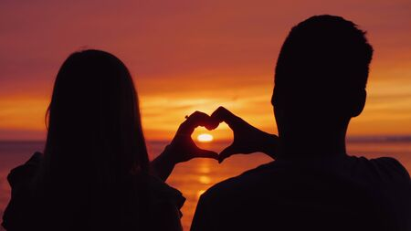 Silhouettes of a young couple, hands show the shape of the heart against the backdrop of the sunset over the sea