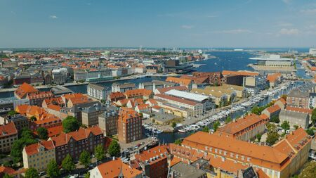 Pan shot of Copenhagen, view from the heights. Houses with traditional tiled roofs and a river.