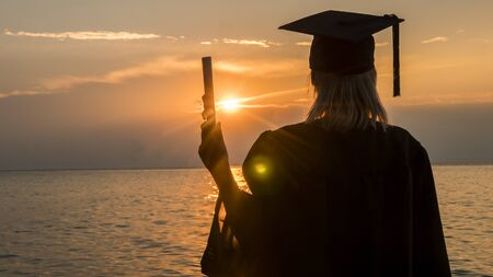 Rear view of a college graduate with a diploma in his hand on a sunset background over the sea. New opportunities with higher education