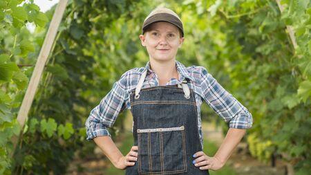 Portrait of a farmer woman near a well-kept garden