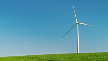 Idyllicistic landscape of a green meadow and a wind generator. Ecology and environment concept.