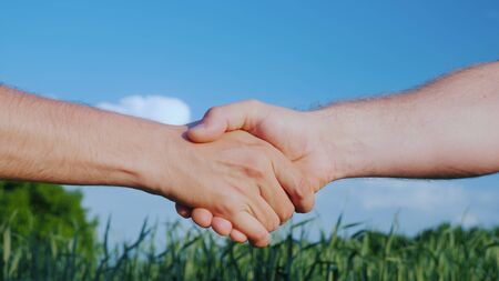Two male farmers shake hands. Against the background of a green field and a blue sky. Deal in agribusiness concept