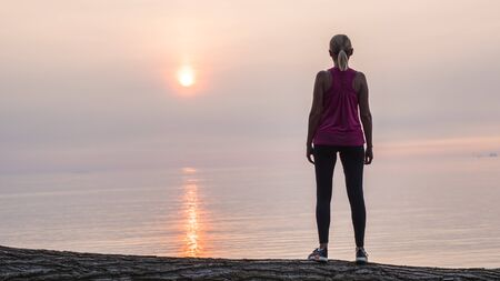 Confident fitness woman looking at dawn over the sea, rear view